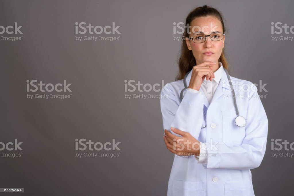 Studio shot of beautiful woman doctor against gray background stock photo
