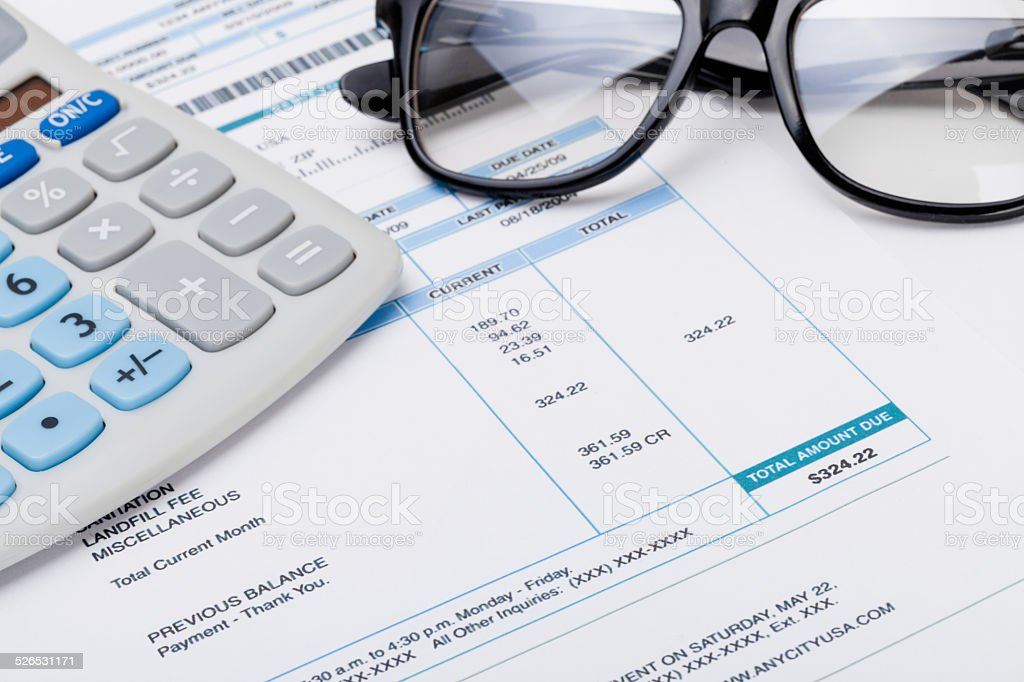 Studio shot of calculator and glasses over some receipt stock photo