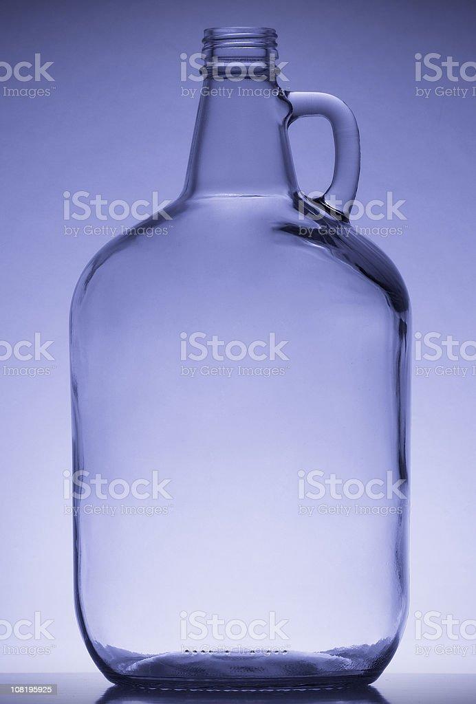 Studio Shot of Empty Glass Jug on Blue Background royalty-free stock photo
