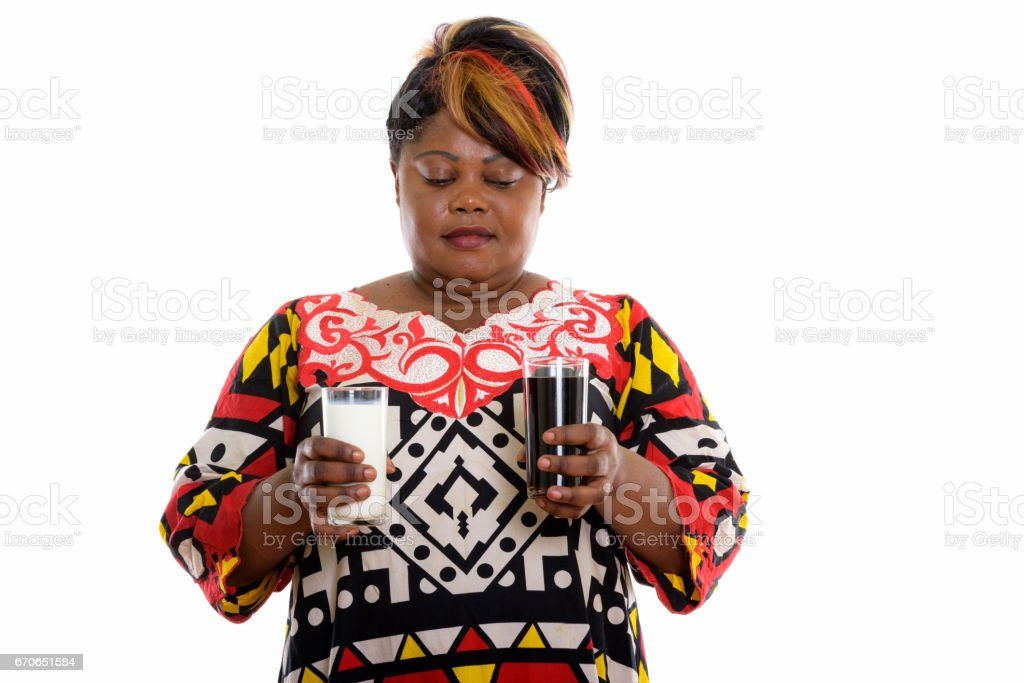 Studio shot of fat black African woman holding glass of milk and looking at glass of soda drink stock photo