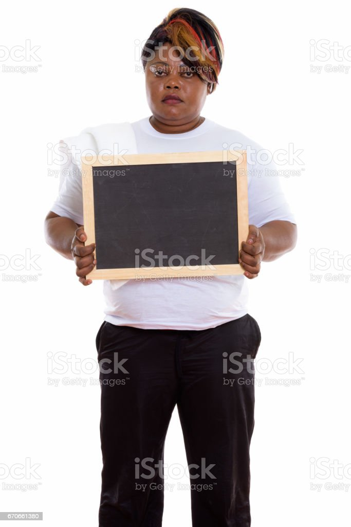 Studio shot of fat black African woman standing while holding blank blackboard ready for gym stock photo