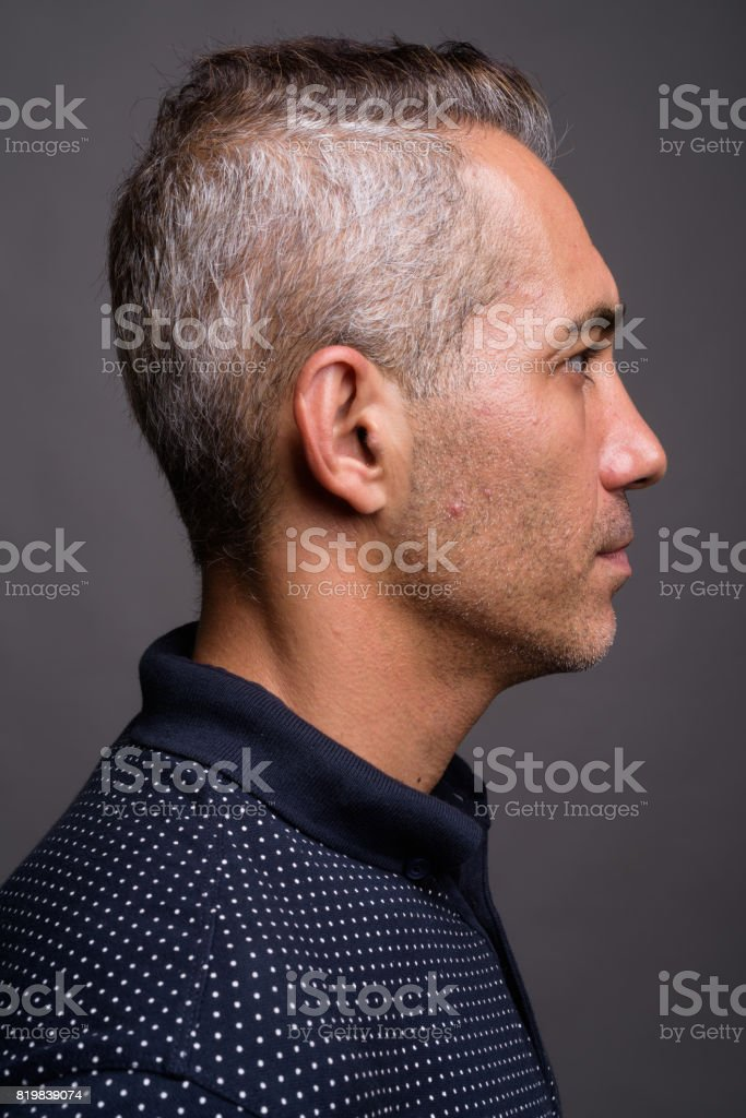Studio shot of handsome man with gray hair wearing blue polo shirt against gray background stock photo