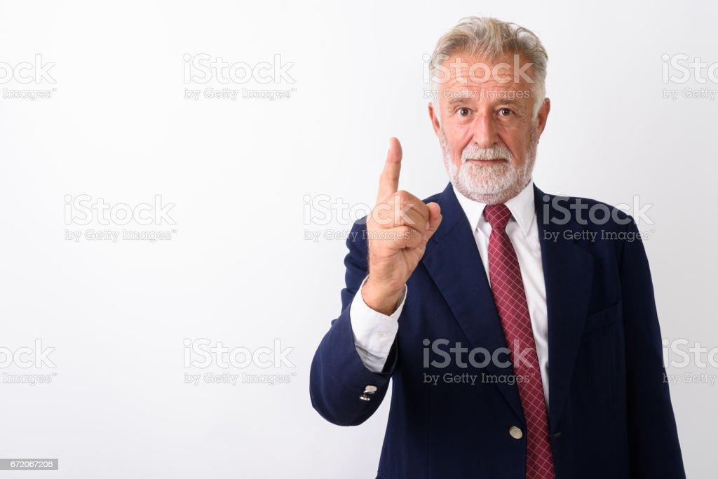 Studio shot of handsome senior bearded businessman pointing finger up against white background stock photo