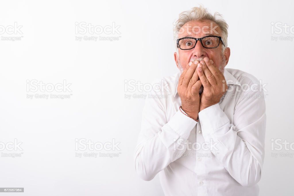 Studio shot of handsome senior bearded man looking shocked while covering mouth with both hands and wearing eyeglasses against white background stock photo