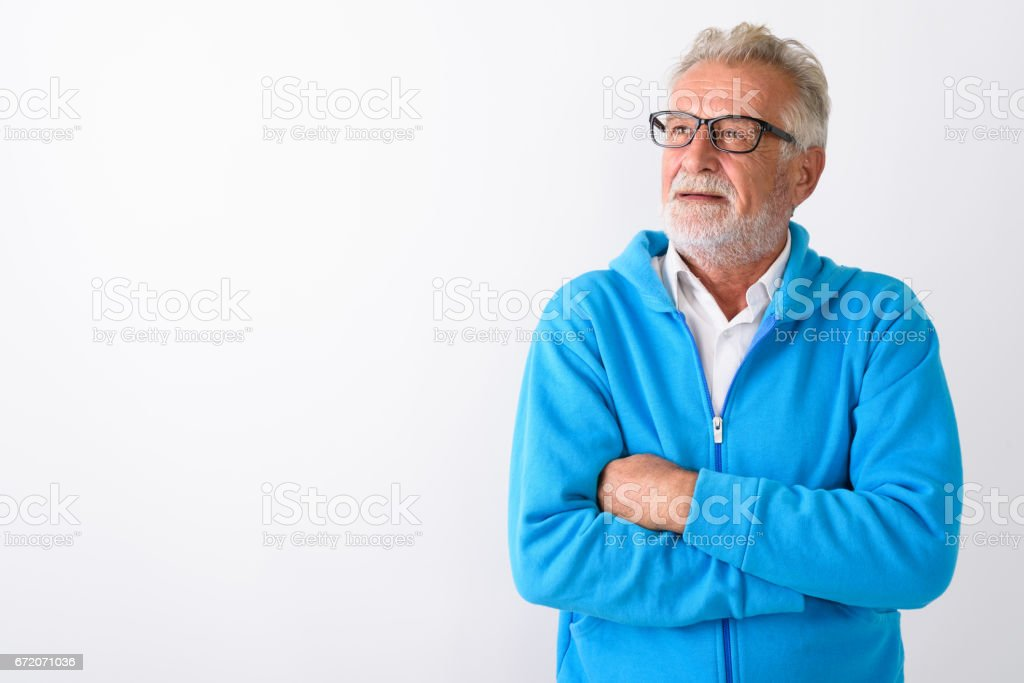 Studio shot of handsome senior bearded man thinking with arms crossed ready for gym against white background stock photo