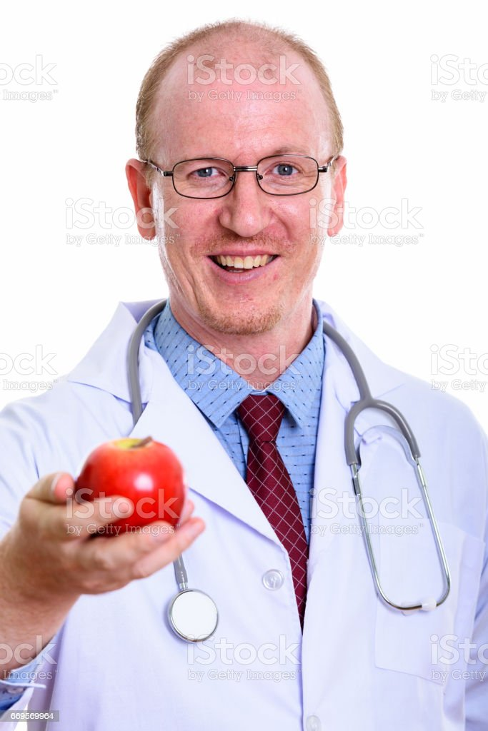 Studio shot of happy man doctor smiling while giving red apple stock photo