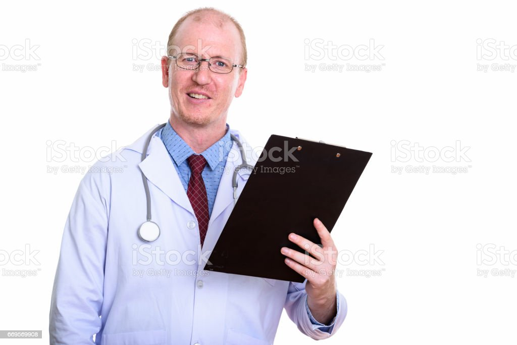 Studio shot of happy man doctor smiling while holding clipboard stock photo