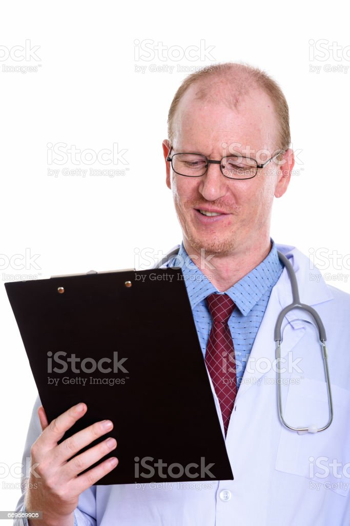 Studio shot of happy man doctor smiling while reading on clipboard stock photo