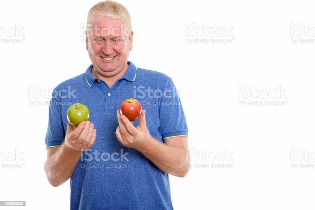 Studio shot of happy mature man smiling while holding and looking at red apple and green apple stock photo