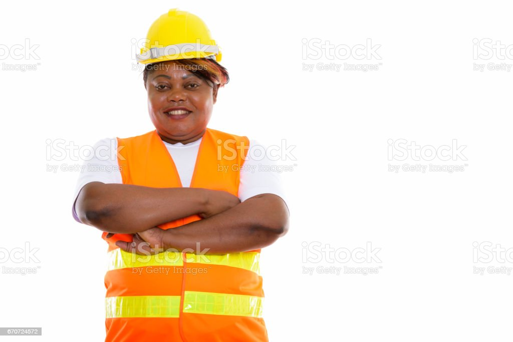 Studio shot of happy fat black African woman construction worker smiling with arms crossed stock photo