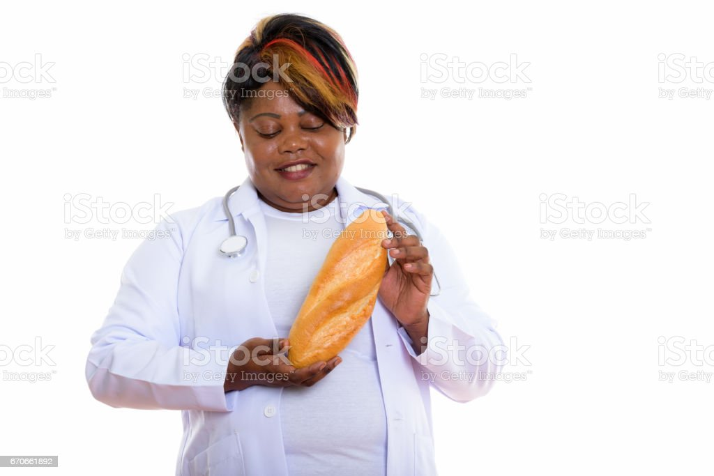 Studio shot of happy fat black African woman doctor smiling while holding and looking at bread stock photo