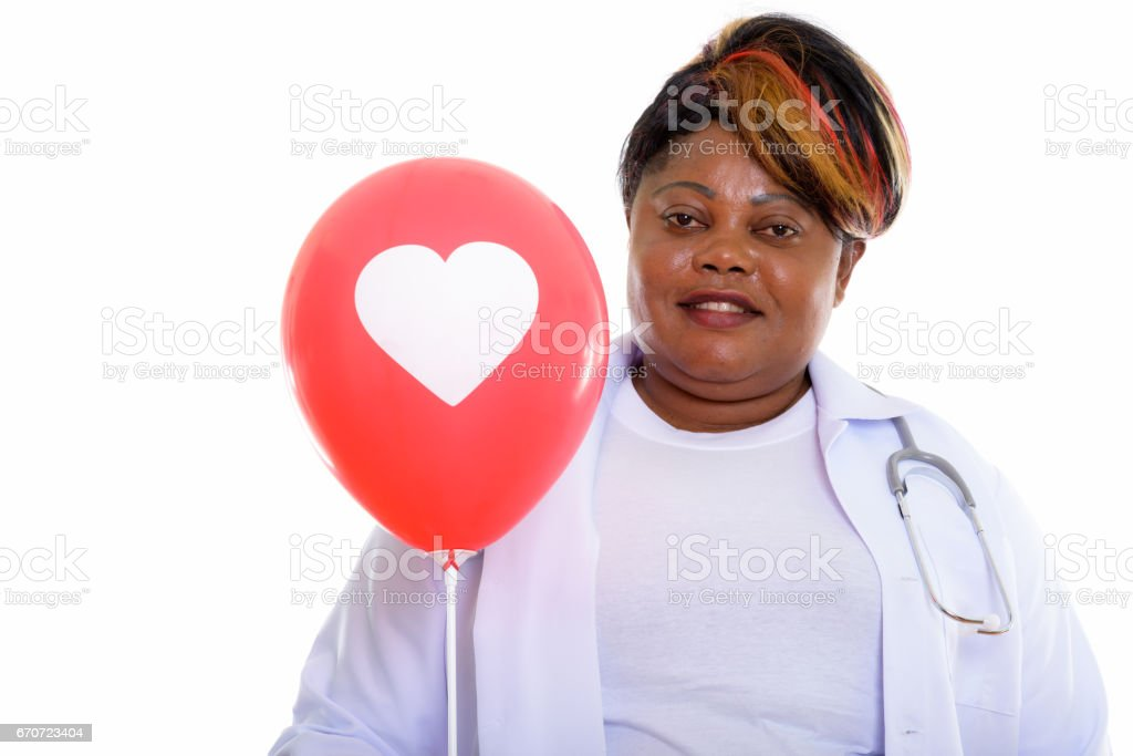 Studio shot of happy fat black African woman doctor smiling while holding red balloon with heart sign stock photo