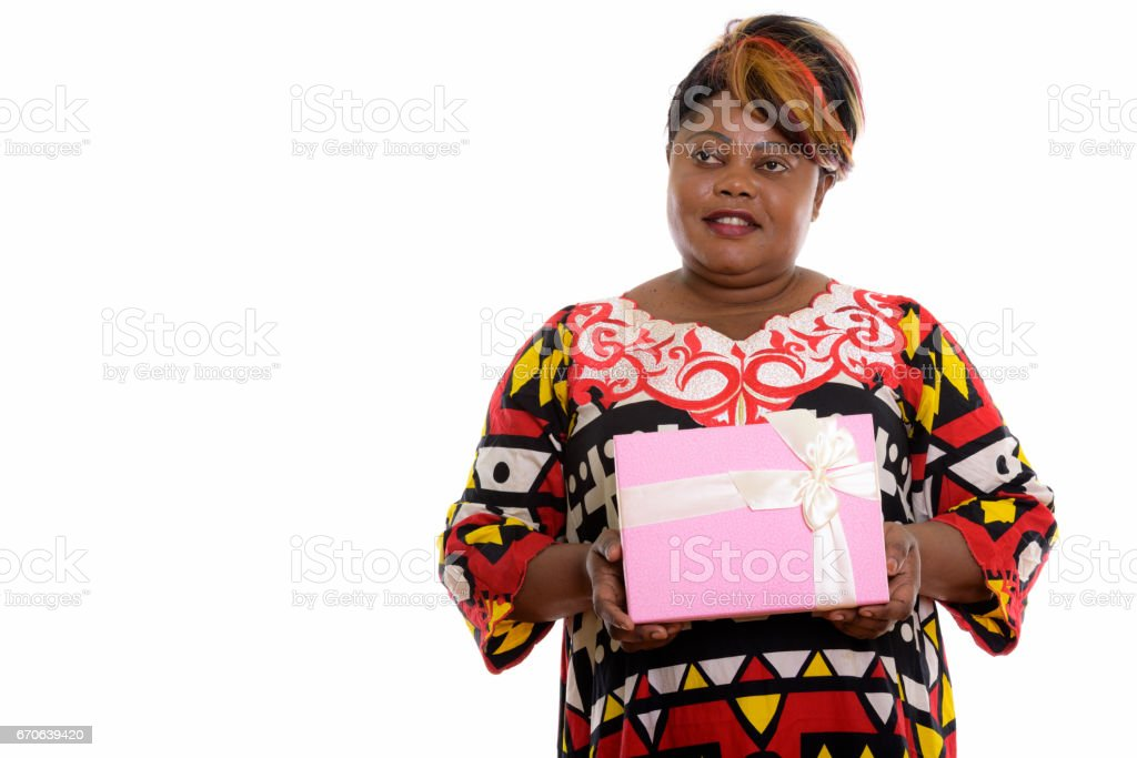 Studio shot of happy fat black African woman smiling and holding gift box while thinking stock photo