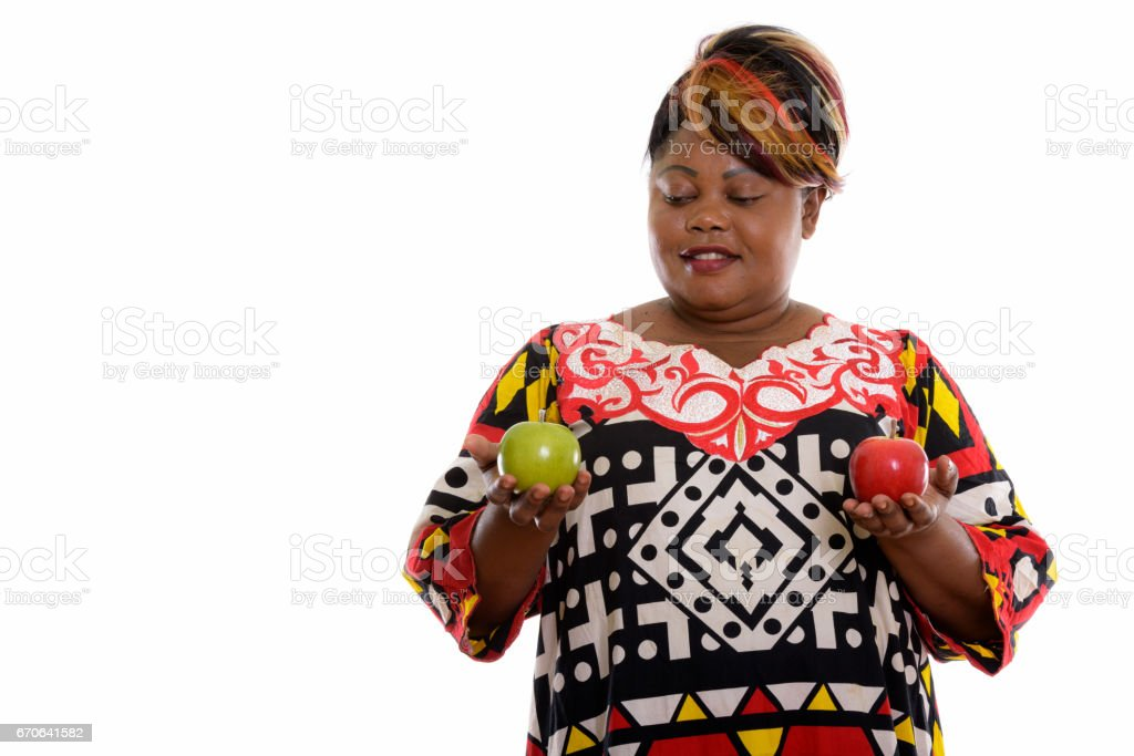 Studio shot of happy fat black African woman smiling while looking at green apple and holding red apple stock photo
