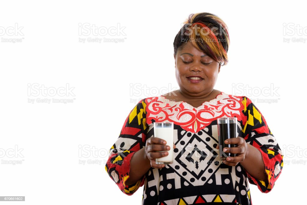 Studio shot of happy fat black African woman smiling while looking at glass of milk and holding glass of soda drink stock photo