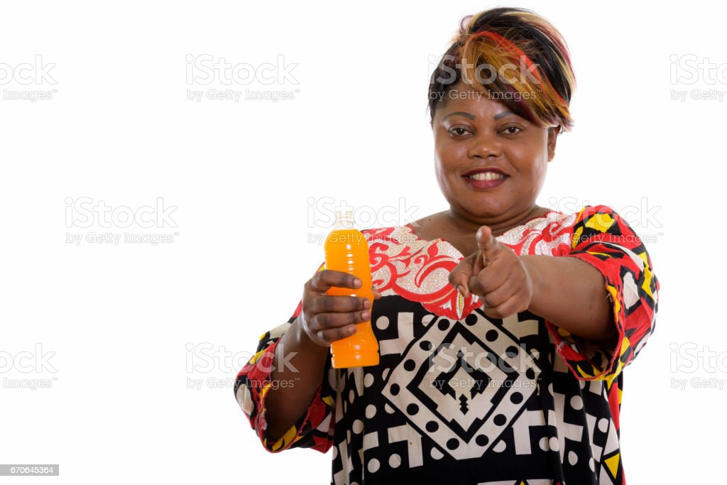 Studio shot of happy fat black African woman smiling while holding bottle of orange juice and pointing at camera stock photo