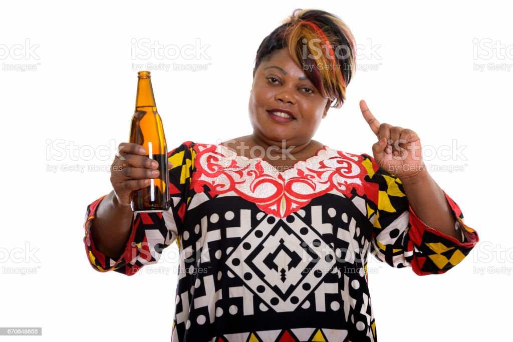 Studio shot of happy fat black African woman smiling while holding bottle of beer and pointing finger up stock photo