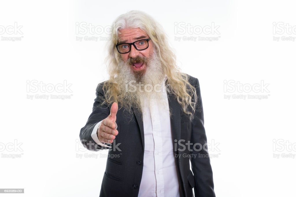 Studio shot of happy senior bearded businessman smiling while giving handshake stock photo