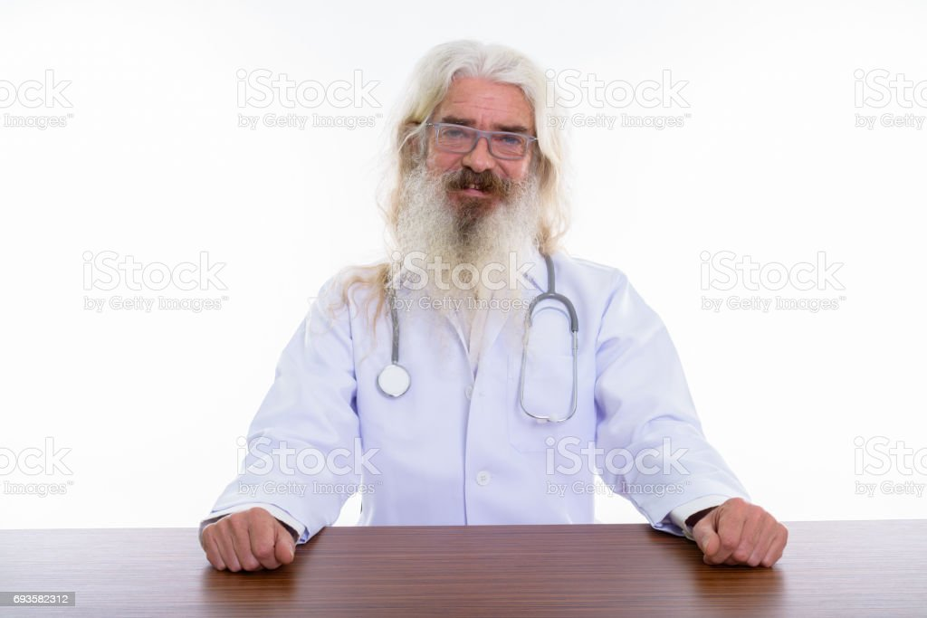 Studio shot of happy senior bearded man doctor smiling while  wearing eyeglasses and sitting on wooden table stock photo