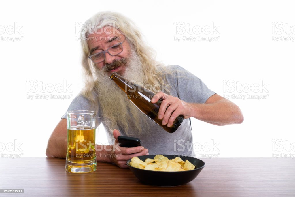 Studio shot of happy senior bearded man smiling while holding mobile phone and pouring beer with bowl of potato chips on wooden table stock photo