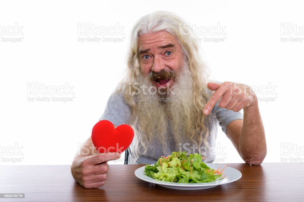 Studio shot of happy senior bearded man smiling while holding red heart and pointing at plate of salad on wooden table stock photo