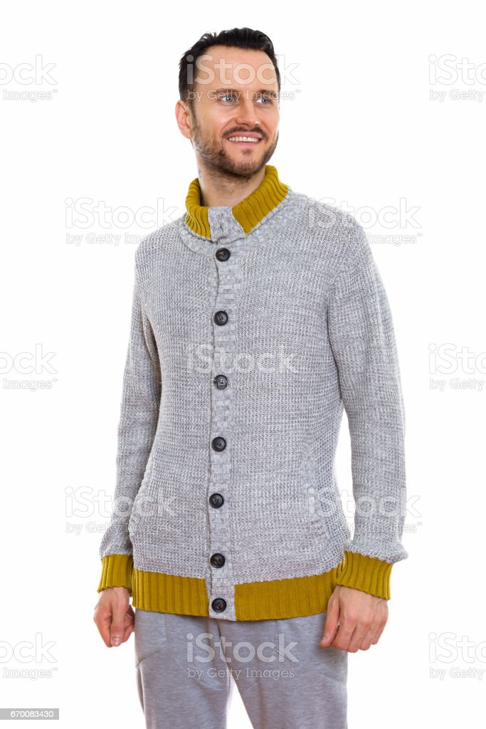 Studio shot of happy young man smiling and standing while thinking stock photo