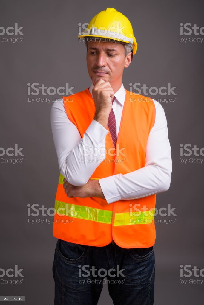 Studio shot of man construction worker against gray background stock photo