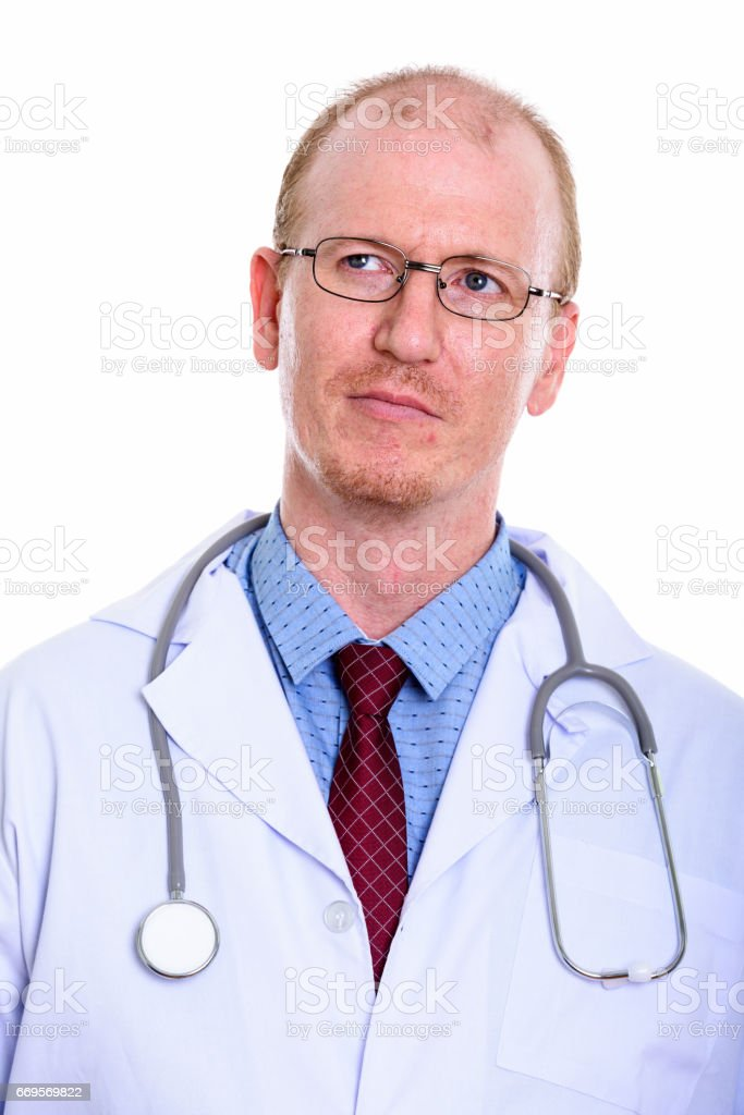 Studio shot of man doctor thinking while looking up stock photo