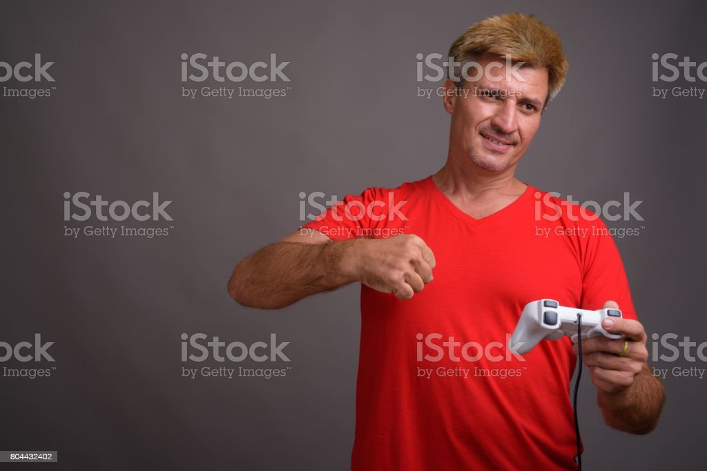 Studio shot of man with blond hair wearing red shirt against gray background stock photo