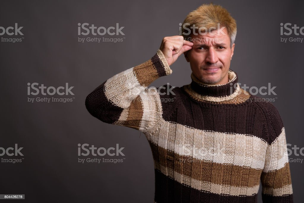 Studio shot of man with blond hair wearing sweater against gray background stock photo