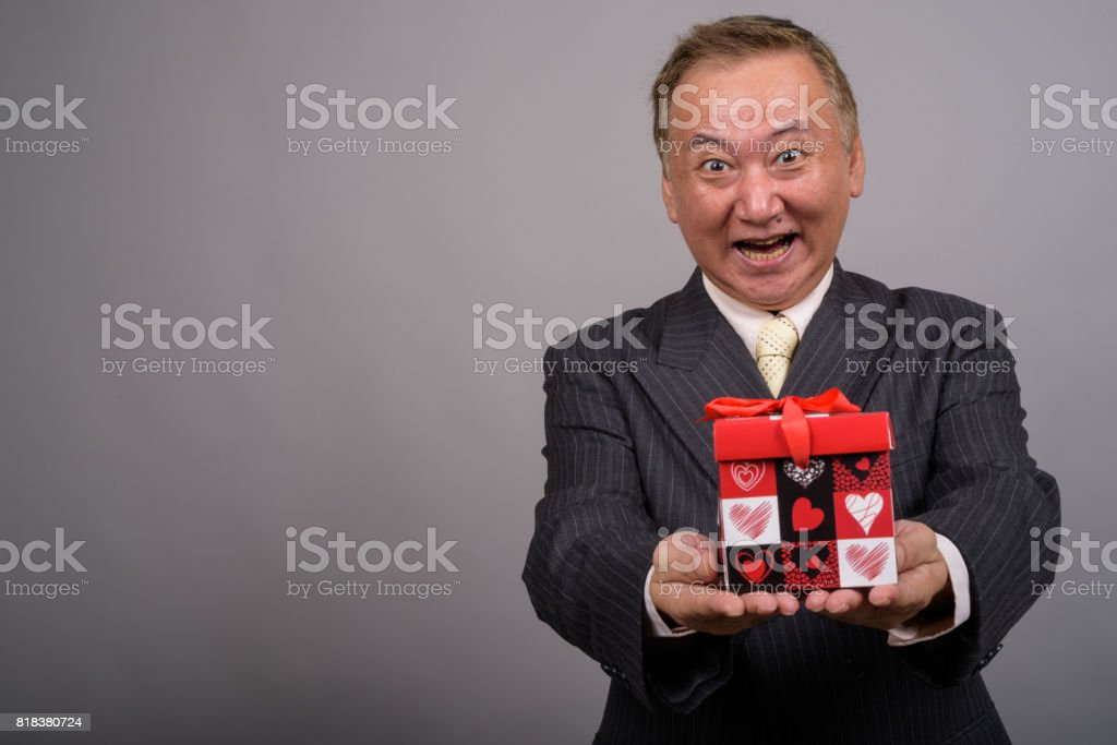 Studio shot of mature Asian businessman holding gift box ready for Valentine's day against gray background stock photo