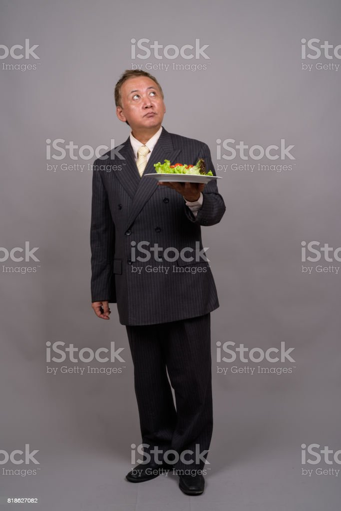 Studio shot of mature Asian businessman holding plate of salad against gray background stock photo