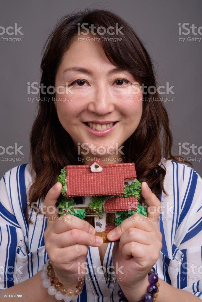 Studio shot of mature beautiful Asian businesswoman against gray background stock photo