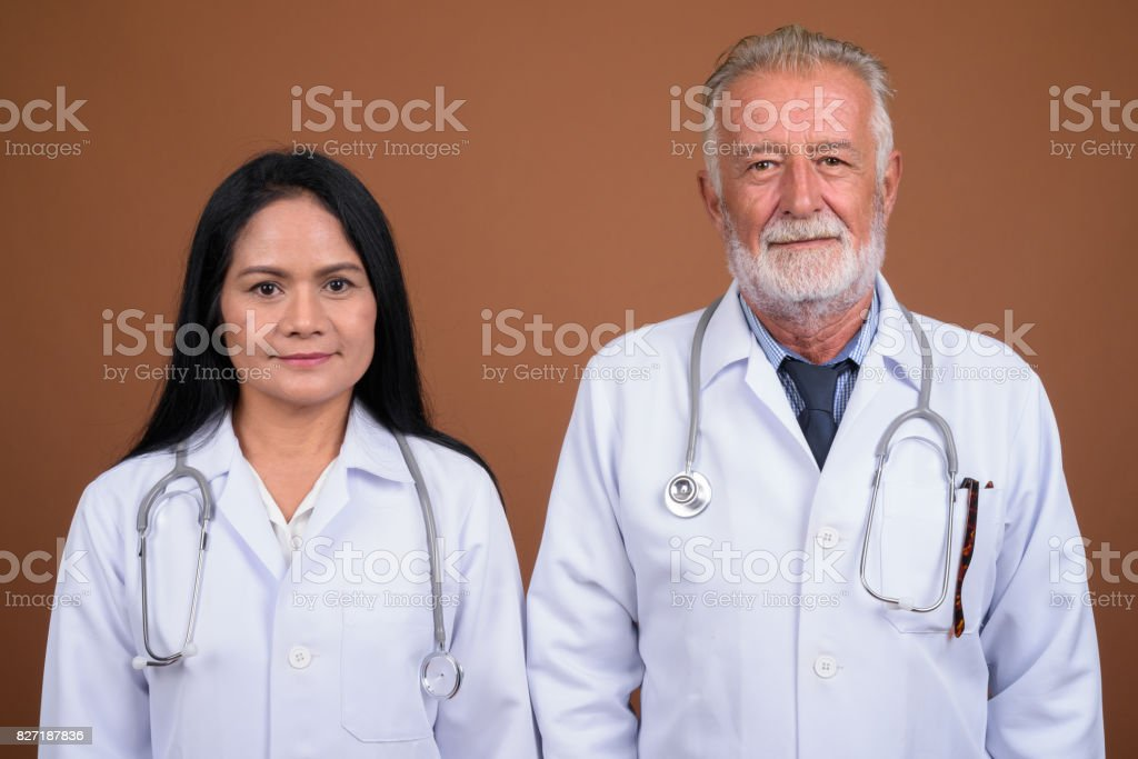 Studio shot of mature multi-ethnic couple doctors against colored background stock photo