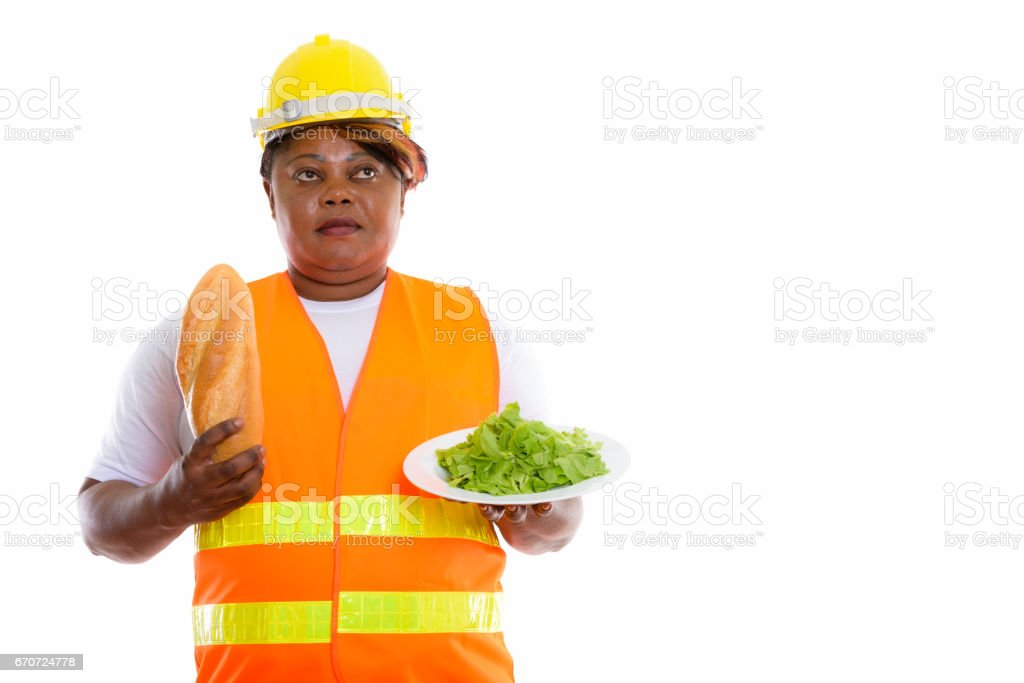Studio shot of fat black African woman construction worker thinking while holding bread and lettuce served on white plate stock photo