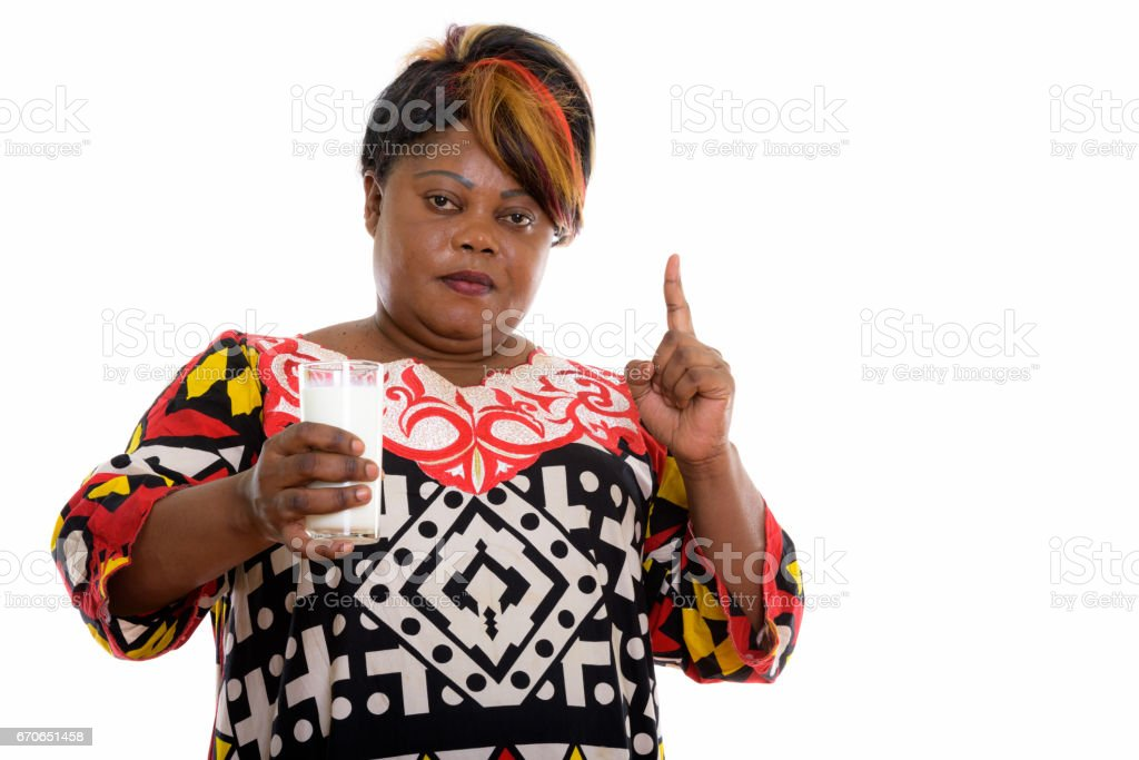 Studio shot of fat black African woman holding glass of milk and pointing finger up stock photo