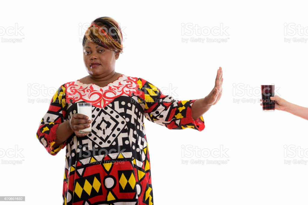 Studio shot of fat black African woman holding glass of milk while rejecting glass of soda drink stock photo