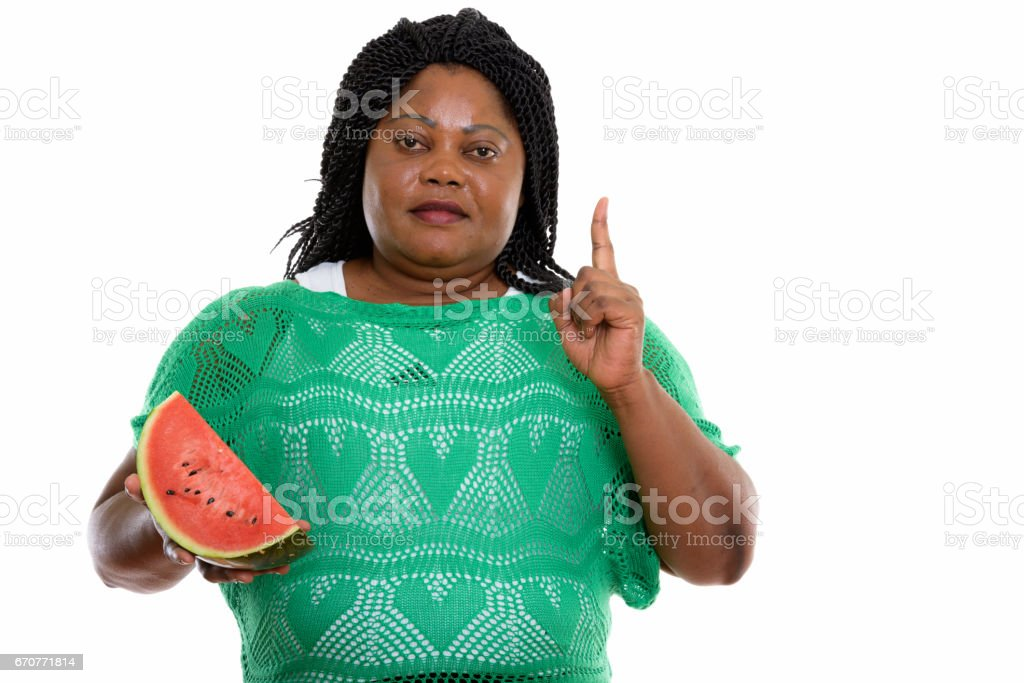 Studio shot of fat black African woman holding slice of watermelon and pointing finger up stock photo