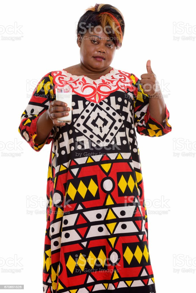 Studio shot of fat black African woman standing while holding glass of milk and giving thumb up stock photo
