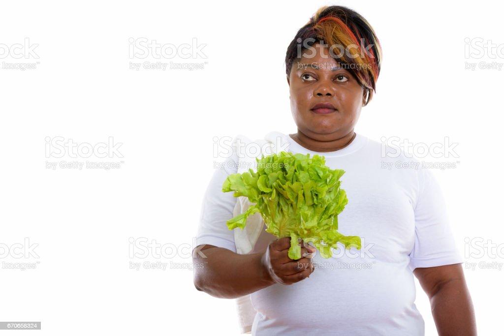 Studio shot of plus-size black African woman thinking while holding lettuce stock photo