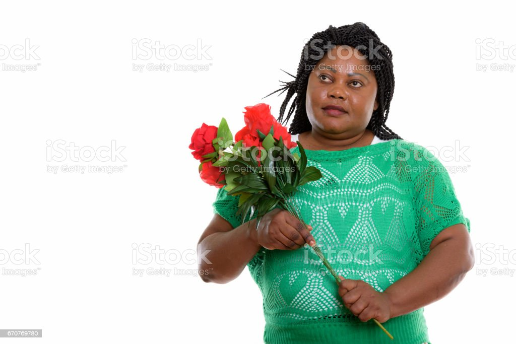 Studio shot of plus-size black African woman thinking while holding red roses ready for Valentine's day stock photo