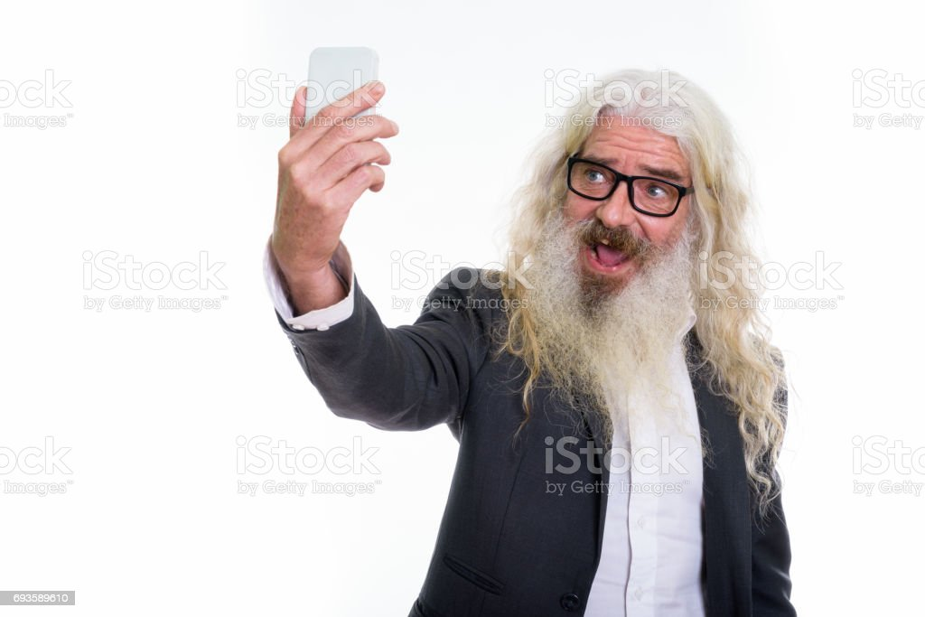 Studio shot of senior bearded businessman taking selfie picture with mobile phone stock photo
