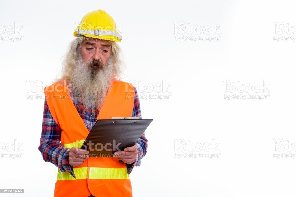 Studio shot of senior bearded man construction worker looking at clipboard stock photo