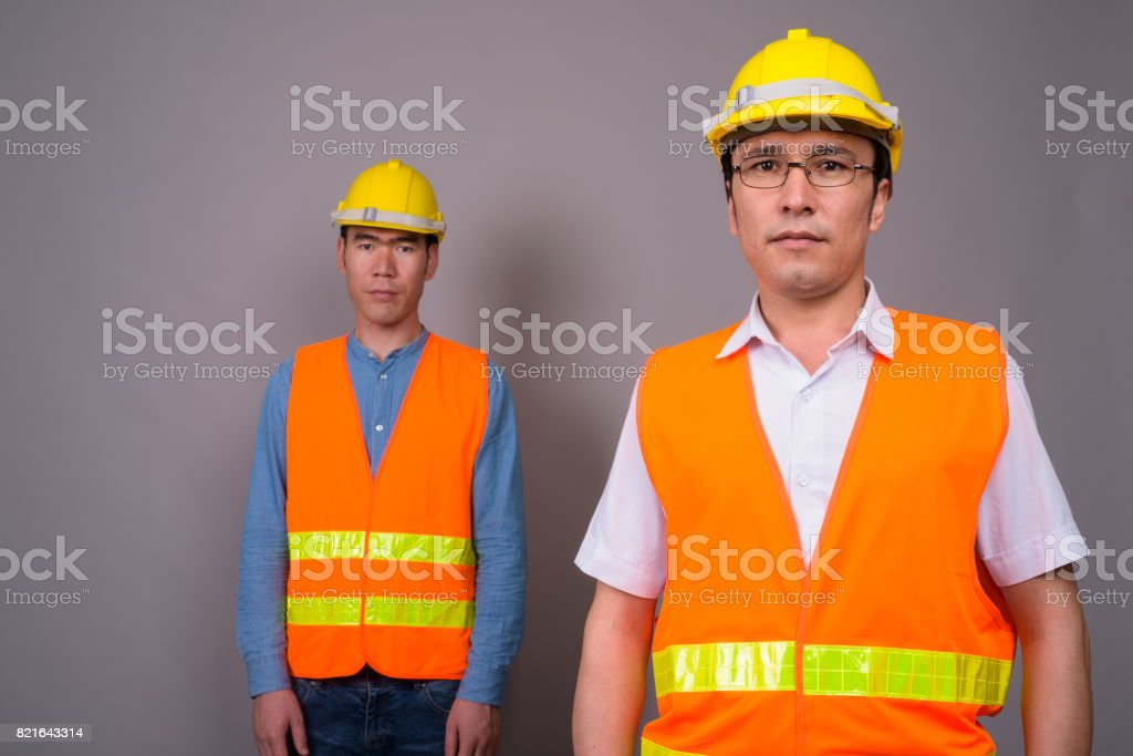 Studio shot of two young Asian man construction worker against gray background stock photo