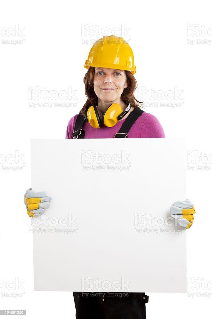 Studio shot of woman wearing hard hat holding blank sign royalty-free stock photo