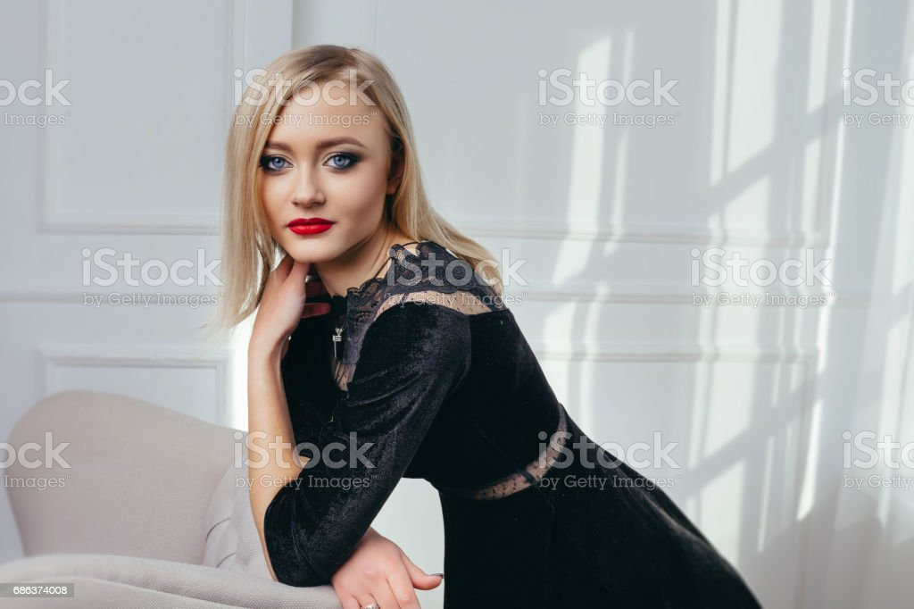 Studio shot of young and beautiful girl in black dress wearing in studio. Blonde girl stock photo