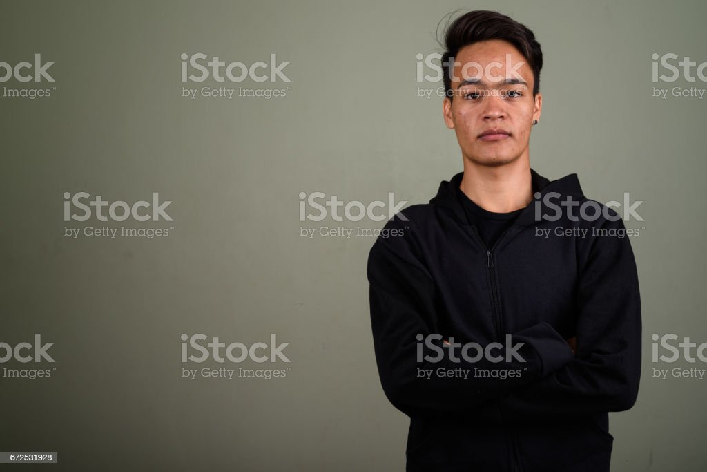 Studio shot of young Asian man against colored background stock photo