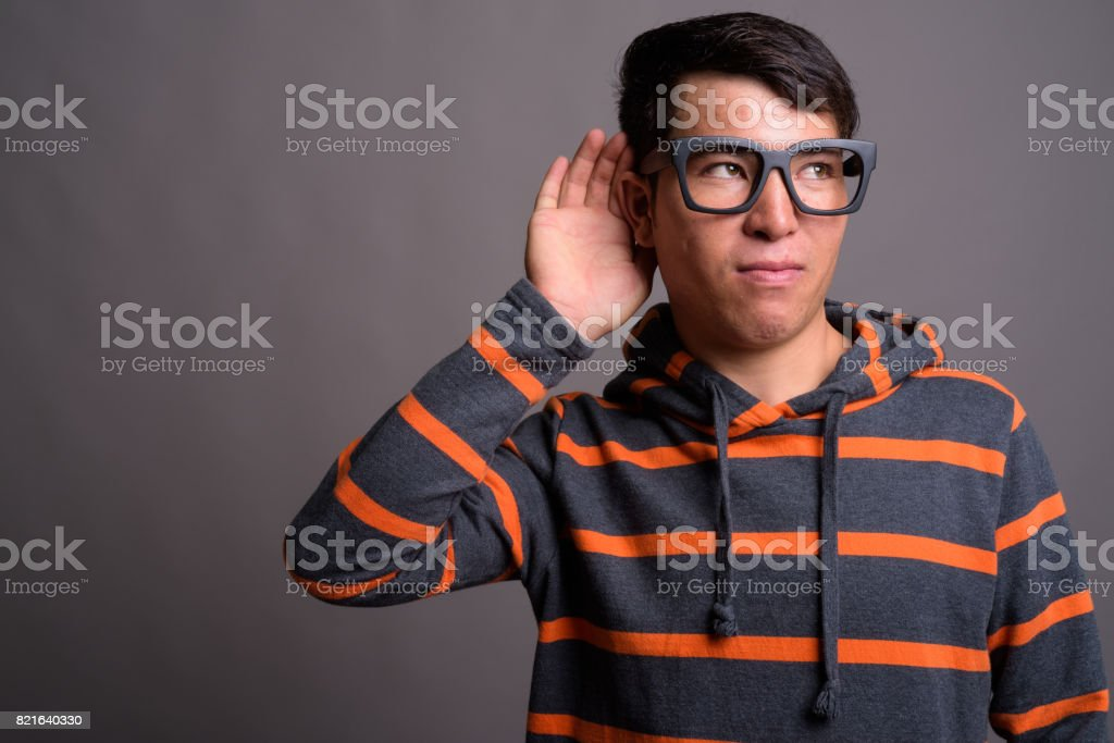 Studio shot of young Asian man wearing hoodie with eyeglasses against gray background stock photo