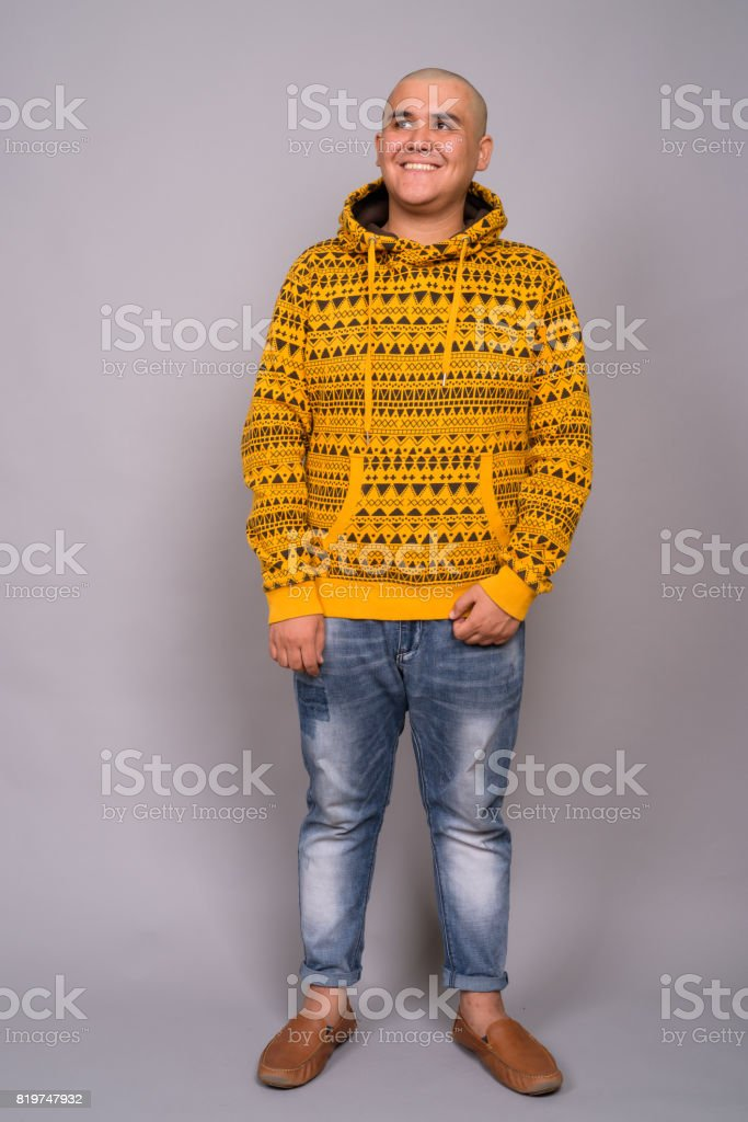 Studio shot of young bald Asian man wearing hoodie against gray background stock photo