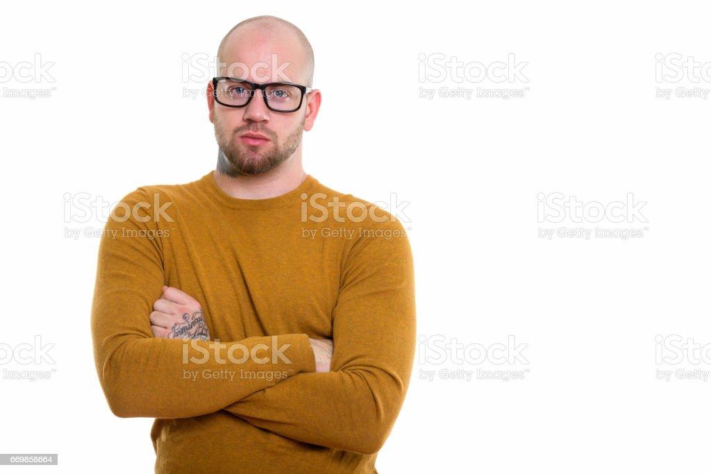 Studio shot of young bald muscular man wearing eyeglasses with arms crossed stock photo